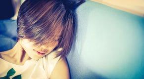 Adolescente japonés del pelo corto que duerme en el sofá Foto de archivo libre de regalías