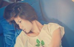 Adolescente japonés del pelo corto que duerme en el sofá Foto de archivo