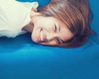 Adolescente japonés del pelo corto que miente en el sofá Imagenes de archivo