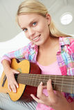 Adolescente jouant la guitare acoustique Photographie stock libre de droits