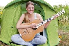 Adolescente jouant sur la guitare près de la tente Images stock