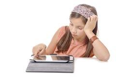 Adolescente joven asentado mirando una tableta Imagen de archivo