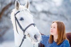 Adolescente joven con el caballo blanco en parque del invierno Fotos de archivo
