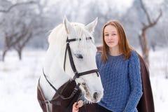 Adolescente joven con el caballo blanco en parque del invierno Fotos de archivo libres de regalías
