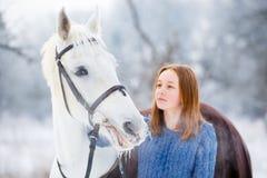 Adolescente joven con el caballo blanco en parque del invierno Foto de archivo