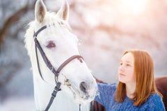 Adolescente joven con el caballo blanco en parque del invierno Imagen de archivo libre de regalías