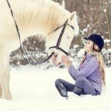 Adolescente joven con el caballo blanco en parque del invierno Foto de archivo libre de regalías