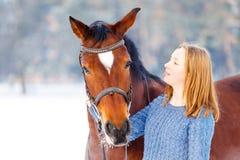 Adolescente joven con el caballo de bahía en parque del invierno Imágenes de archivo libres de regalías
