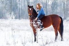 Adolescente joven con el caballo de bahía en parque del invierno Imagenes de archivo