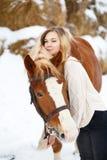 Adolescente joven con el caballo en parque del invierno Imagenes de archivo