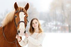 Adolescente joven con el caballo en parque del invierno Imagen de archivo libre de regalías