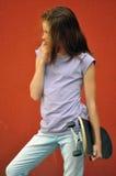 Adolescente joven con el monopatín en la calle Foto de archivo libre de regalías