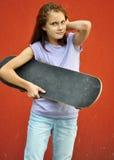 Adolescente joven con el monopatín en la calle Foto de archivo