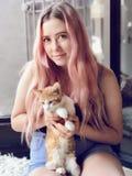 Adolescente joven con el pelo largo que sostiene gatos del animal doméstico Fotografía de archivo
