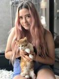 Adolescente joven con el pelo largo que sostiene gatos del animal doméstico Fotos de archivo