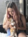 Adolescente joven con el pelo largo que sostiene gatos del animal doméstico Fotos de archivo libres de regalías