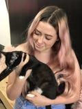 Adolescente joven con el pelo largo que sostiene un gato negro del animal doméstico Imagenes de archivo