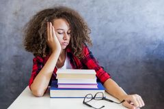 Adolescente joven con el pelo rizado que descansa del aprendizaje Fotografía de archivo