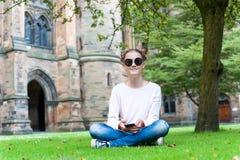 Adolescente joven con el smartphone que se sienta en Glasgow University Imagen de archivo libre de regalías