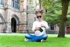 Adolescente joven con el smartphone que se sienta en Glasgow University Foto de archivo libre de regalías