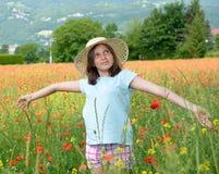 Adolescente joven con el sombrero en campo de la amapola Imagen de archivo libre de regalías