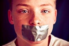 Adolescente joven con la boca de la cubierta de la cinta aislante Fotos de archivo