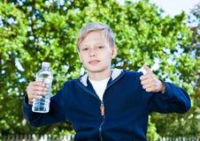 Adolescente joven con la botella de agua en parque Fotos de archivo