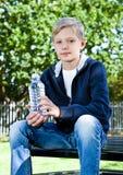 Adolescente joven con la botella de agua en parque Imagenes de archivo
