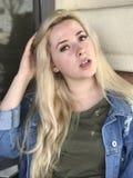 Adolescente joven con la chaqueta larga del pelo rubio y del dril de algodón Imágenes de archivo libres de regalías