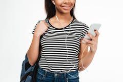 Adolescente joven con la mochila que escucha la música a través de los auriculares Imagenes de archivo