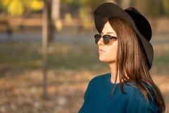 Adolescente joven con las gafas de sol y el sombrero negro que miran en el sol con el fondo borroso Imagenes de archivo