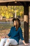Adolescente joven con las gafas de sol y el sombrero negro que miran en el sol con el fondo borroso Foto de archivo libre de regalías