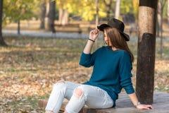 Adolescente joven con las gafas de sol y el sombrero negro que miran en el sol con el fondo borroso Fotografía de archivo libre de regalías