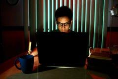 Adolescente joven con las lentes delante de un ordenador portátil Foto de archivo libre de regalías