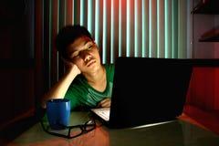 Adolescente joven con las lentes y agujereado delante de un ordenador portátil Imagen de archivo