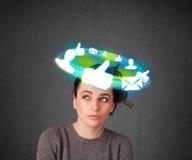 Adolescente joven con los iconos sociales de la nube alrededor de su cabeza Fotografía de archivo