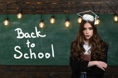 Adolescente joven con los libros de escuela Colegiala linda que presenta solucionando problema en la pizarra Aliste para la escue imagenes de archivo