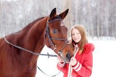 Adolescente joven con su caballo en parque del invierno Fotos de archivo
