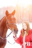 Adolescente joven con su caballo en parque del invierno Imágenes de archivo libres de regalías