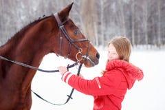 Adolescente joven con su caballo en parque del invierno Fotos de archivo libres de regalías