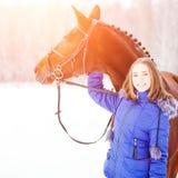Adolescente joven con su caballo en parque del invierno Foto de archivo libre de regalías