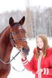Adolescente joven con su caballo en parque del invierno Fotografía de archivo