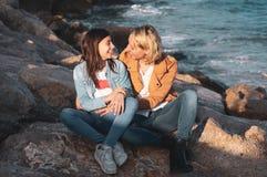 Adolescente joven con su madre en gesto cariñoso por el mar Vacaciones de familia en la costa imágenes de archivo libres de regalías