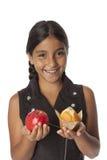 Adolescente joven con una manzana y un mollete Foto de archivo
