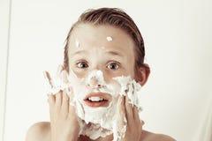 Adolescente joven de la diversión que mancha su cara con espuma Fotos de archivo libres de regalías