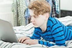 Adolescente joven de moda que usa un ordenador portátil Fotografía de archivo libre de regalías