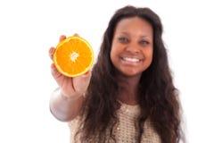 Adolescente joven del afroamericano que sostiene una naranja cortada Fotos de archivo