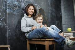Adolescente joven del inconformista que se sienta con su hermano en multinacional de la sala de clase Fotos de archivo libres de regalías