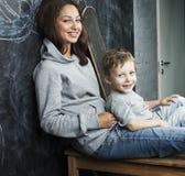 Adolescente joven del inconformista que se sienta con su hermano en multinacional de la sala de clase Foto de archivo libre de regalías