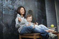 Adolescente joven del inconformista que se sienta con su hermano en multinacional de la sala de clase Fotografía de archivo